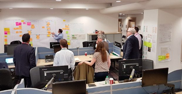 Group in an office looking at whiteboard with post it notes on