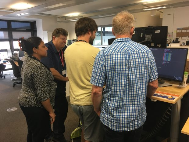 People stand around a desk looking at a display screen